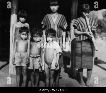 AJAXNETPHOTO. 1953-1957 (APPROX). INDO CHINA. VIETNAM. (IN-COUNTRY LOCATION UNKNOWN.) -  GROUP OF GIRLS, ONE SMOKING A BAMBOO WATER PIPE AND YOUNG BOYS POSE FOR THE CAMERA OUTSIDE HOUSE ON STILTS.PHOTO:JEAN CORRE/AJAXREF:RX7_191508_242 - Stock Photo