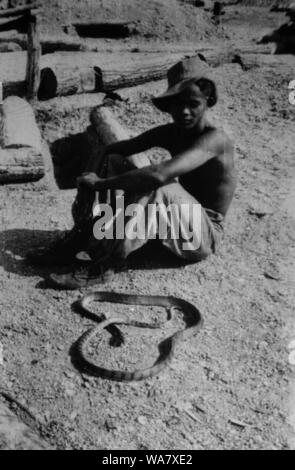 AJAXNETPHOTO. 1953-1957 (APPROX). INDO CHINA. VIETNAM. (IN-COUNTRY LOCATION UNKNOWN.) -  MAN SITTING WITH SNAKE.PHOTO:JEAN CORRE/AJAXREF:RX7_191508_231 - Stock Photo