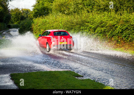 Car driving through water along a flooded country road / lane during wet weather after a heavy rain storm - Stock Photo