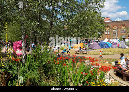 Tents, people and flower garden in park at Extinction Rebellion protest in Waterloo Millennium Green in South London SE1  England UK  KATHY DEWITT - Stock Photo