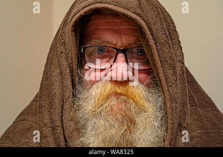 Elderly man wearing hooded blanket to keep warm - Stock Photo