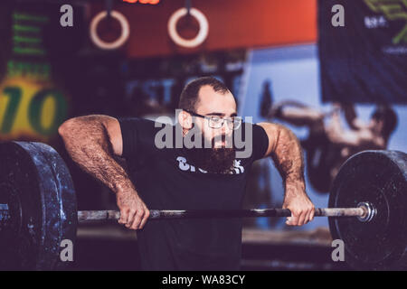 Young bearded man in sportswear straining to lift heavy weights during a workout session in a gym - Stock Photo