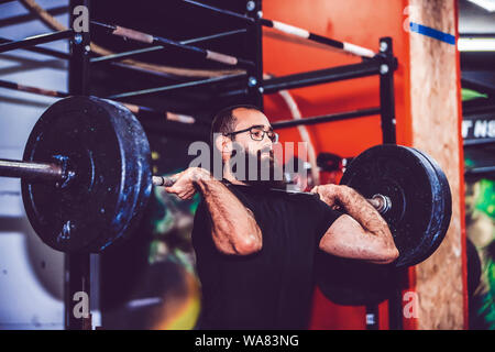Young bearded man straining to lift heavy weights during a workout session in a gym - Stock Photo
