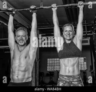 An attractive middle aged couple is doing a fitness training together and having fun. Athletic older man and woman are hanging on the horizontal bar. - Stock Photo