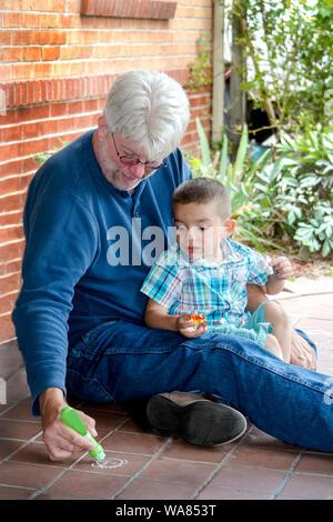 child drawing with grandpa using sidewalk chalk - Stock Photo