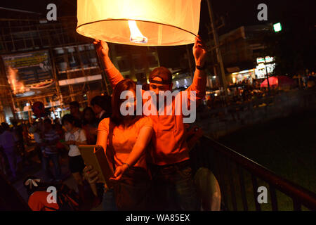 A young Thai lovers couple taking a selfie before launching a flying lantern to celebrate the annual Loy Krathong festival. Chiang Mai, City Center, Chiang Mai Province, Thailand, South East Asia - Stock Photo