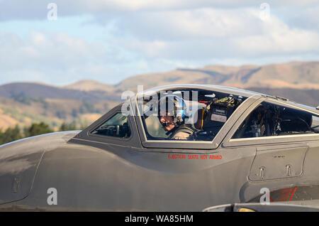 de Havilland Vampire jet plane at Wings over Wairarapa airshow, Hood Aerodrome, Masterton, New Zealand. Pilot in cockpit with Wairarapa hills - Stock Photo