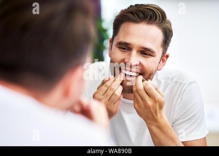 Adult man flossing teeth in the bathroom - Stock Photo