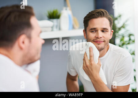 Portrait of adult man shaving in the bathroom - Stock Photo