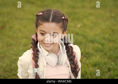 Secrets to raising happy child. Girl cute kid green grass background. Healthy emotional happy kid relaxing outdoors. Get happy yourself. Girl modern headphones enjoy relax. Look on bright side. - Stock Photo