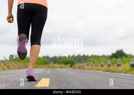 Closeup woman running towards on the road side. Step, run and outdoor exercise activities concept. - Stock Photo