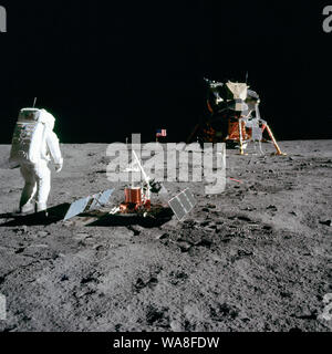 Astronaut Edwin E.'Buzz' Aldrin Jr., Lunar Module pilot, is photographed during the Apollo 11 extravehicular activity on the Moon. He has just deployed the Early Apollo Scientific Experiments Package (EASEP). In the foreground is the Passive Seismic Experiment Package (PSEP); beyond it is the Laser Ranging Retro-Reflector (LR-3); in the center background is the United States flag; in the left background is the black and white lunar surface television camera; in the far right background is the Lunar Module 'Eagle'. Astronaut Neil A. Armstrong, commander, took this photograph with a 70mm lunar s - Stock Photo