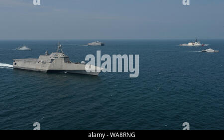 190816-N-NI298-0052  LUMUT, Malaysia (Aug 16, 2019) The U.S. Navy, U.S. Coast Guard, Royal Malaysian Navy (RMN), and Malaysian Maritime Enforcement Agency (MMEA) sail side-by-side in formation as part of the at-sea portion of Maritime Training Activity (MTA) 2019. U.S. assets featured include the Independence-variant littoral combat ship USS Montgomery (LCS 8), U.S. Coast Guard Cutter Stratton (WMSL 752), expeditionary fast transport ship USNS Millinocket (T-EPF 3), an MH-60S Seahawk helicopter and a MH-65 Dolphin helicopter. RMN assets include Lekiu-class frigate KD Lekiu (F30) and Kasturi-cl - Stock Photo