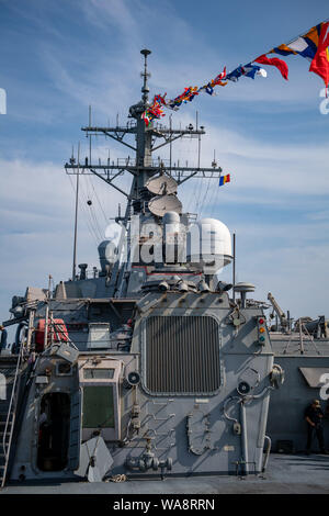 CONSTANTA, Romania (Aug. 15, 2019) — The Arleigh Burke-class guided-missile destroyer USS Porter (DDG 78) sits at full-dress during Romanian Navy Day in Constanta, Romania, Aug. 15, 2019. Porter, forward-deployed to Rota, Spain, is on its seventh patrol in the U.S. 6th Fleet area of operations in support of U.S. national security interests in Europe and Africa. (U.S. Navy photo by Mass Communication Specialist 3rd Class T. Logan Keown/Released) - Stock Photo