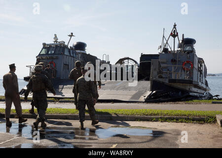 U.S. Marines with Special Purpose Marine Air-Ground Task Force - Southern Command unload heavy equipment from a U.S. Navy landing craft, air cushion (LCAC) to be used for UNITAS LX on the Brazilian Marine Corps Base of Ilha do Governador, Brazil, Aug. 18, 2019. This equipment is used to aid in supporting humanitarian assistance and disaster relief scenarios. UNITAS is the world's longest-running, annual exercise and brings together multinational forces from 11 countries to include Brazil, Colombia, Peru, Chile, Argentina, Ecuador, Panama, Paraguay, Mexico, Great Britain and the United States. - Stock Photo