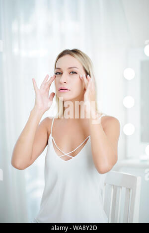 Beautiful young woman in white lace dress applying firming cream under her eyes - Stock Photo