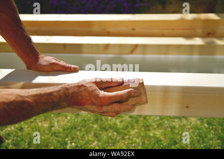 man's hand smoothing natural wooden beam using sandpaper while he is  working outside. Sanding of wood beams spruce for carport. - Stock Photo