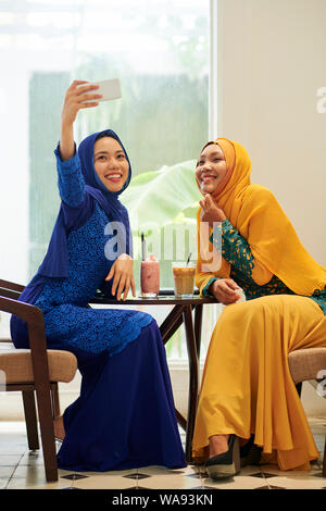 Happy young Asian muslim woman taking selfie with her friend when spending time in cafe - Stock Photo