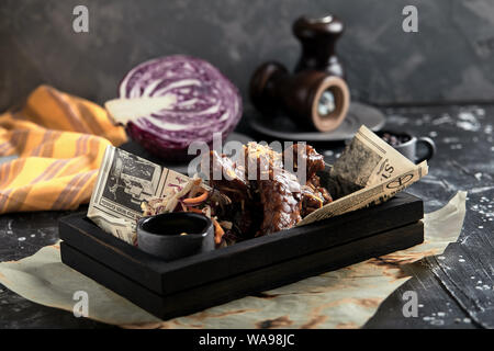Tasty grilled ribs seasoned with spicy sauce and chopped fresh vegetables on an old rustic wooden cutting board with mustard - Stock Photo