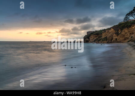 Beautiful long exposure shot of Little Corona del Mar Beach at sunset with smooth waves washing onto the shore and tall cliffs in the background, Coro