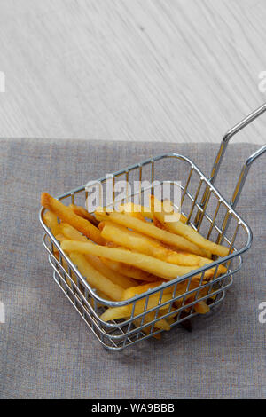 Fries chips in a wire mesh basket with a handle.  Standing on a grey marl tea towel and a grey wood background. - Stock Photo