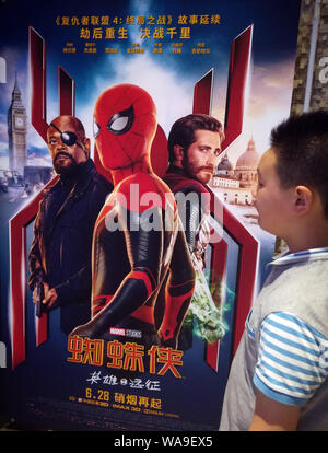 A filmgoer waits in front of a poster of American superhero film 'Spider-Man: Far from Home' at a cinema in Yichang city, central China's Hubei provin - Stock Photo