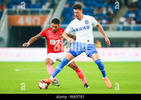German football player Sandro Wagner, right, of Tianjin TEDA passes the ball against Brazilian football player Paulinho of Guangzhou Evergrande Taobao - Stock Photo