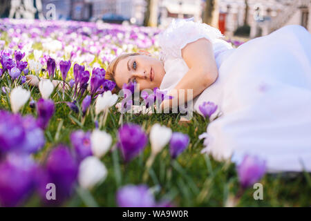 Beautiful young blonde woman with blue eyes wearing in white dress lying on the carpet among the spring flowers crocuses. Spring sunny day. A field of - Stock Photo