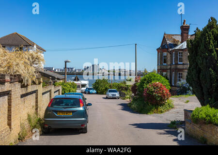 A view down Admiralty Road Upnor in Kent to housing on the opposite side of the River Medway, on St Mary's Island, Chatham, UK Stock Photo