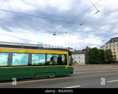 A wide shot of a yellow and green tram on a street near buildings - Stock Photo