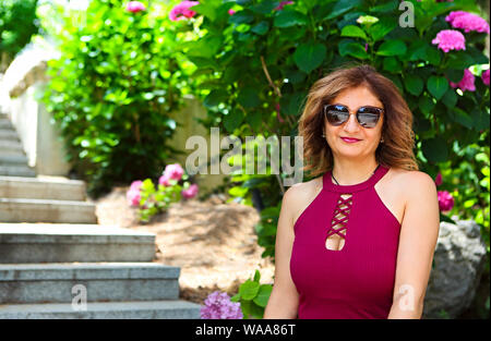 Portrait of a lovely middle aged woman wearing sunglasses having fun outdoors while relaxing in the garden - Stock Photo