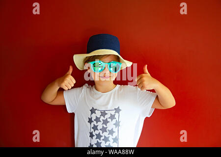 Pretty emothional child wear a hat and sunglasses on a red background. Copy space, daylight - Stock Photo