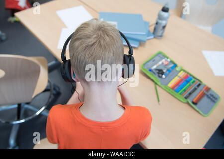 Dresden, Germany. 19th Aug, 2019. A student sits at the edge of an opening ceremony in a classroom of the university school and wears headphones. The public and free primary and secondary school is a joint project of the state capital Dresden and the TU Dresden. Credit: Sebastian Kahnert/dpa-Zentralbild/dpa/Alamy Live News - Stock Photo