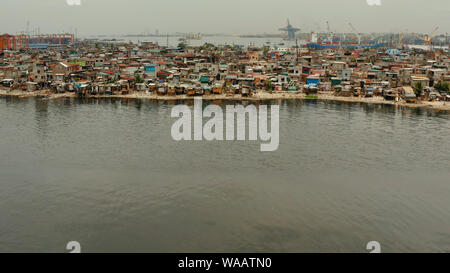 Slum area near port in Manila, Phillippines, top view. lot of garbage in the water. - Stock Photo