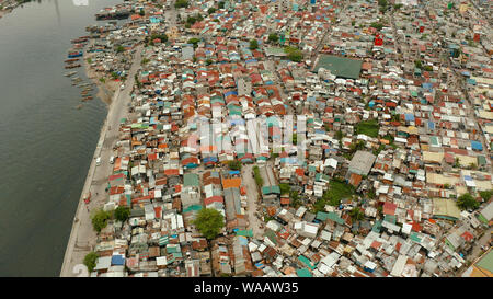 Slum area in Manila, Phillippines, top view. lot of garbage in the water. - Stock Photo