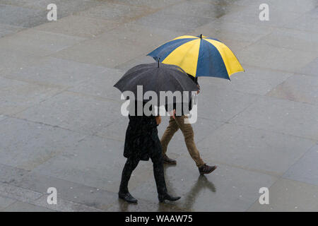 People walking in the rain, Trafalgar Square, London, Britain. - Stock Photo