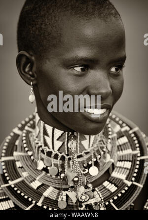 Young beautiful Maasai woman with traditional necklace poses for a portrait in Loitoktok, Kenya. - Stock Photo