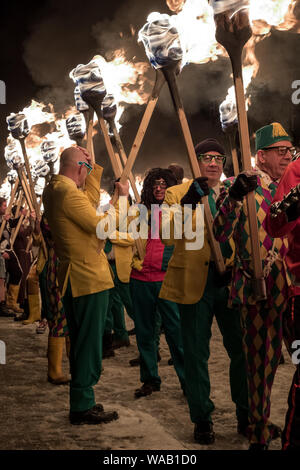 Men in fancy dress carrying fire torches at the Up Helly Aa festival in Lerwick, Shetland - Stock Photo