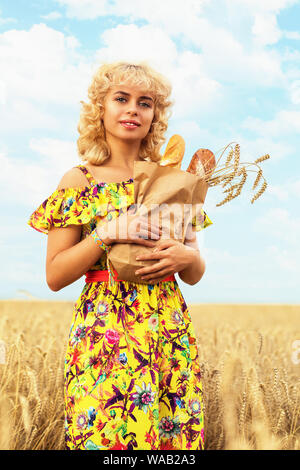 Girl with a full pack of bread in a field with ripe wheat. Model posing on the background of crops ready for harvest - Stock Photo