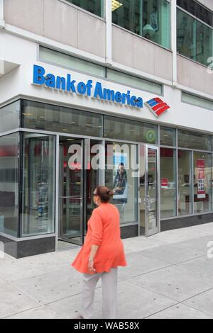 PHILADELPHIA, USA - JUNE 11, 2013: Person walks by Bank of America branch in Philadelphia. Bank of America is the 2nd largest bank holding in the USA - Stock Photo