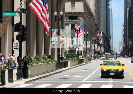 CHICAGO, USA - JUNE 27, 2013: People walk along LaSalle Street in downtown Chicago. Chicago is the 3rd most populous US city with 2.7 million resident - Stock Photo