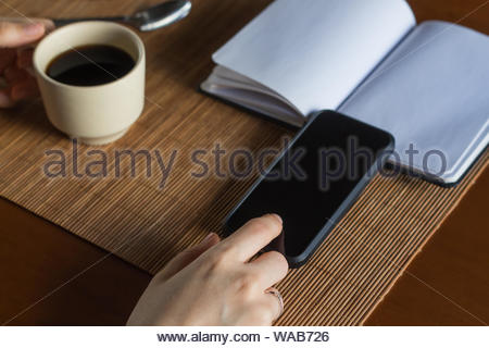 A woman with her smart phone having a cup of coffee and planning business with a notebook - Stock Photo