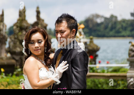 Bali, Indonesia - Mar 25th, 2014  - Newlywed Chinese couple  posing for photos at  Pura Ulun Danu Bratan, Bali. Hindu temple surrounded by flowers on - Stock Photo