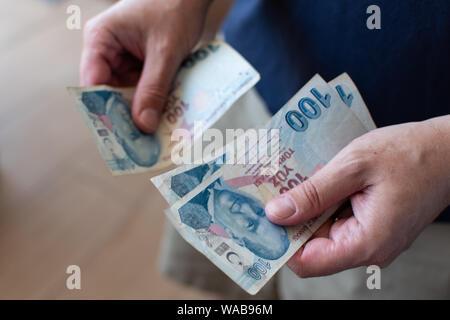 Hands of middle aged caucasian man counting 100 Turkish Lira bank notes in Izmir in Turkey. - Stock Photo