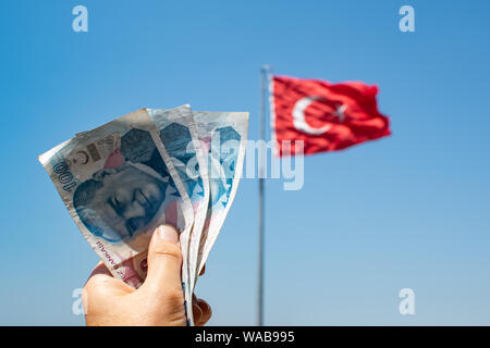 Hands of young  woman holding one hundred Turkish Lira bank notes in front of blurred out Turkish flag and blue sky in the background. Taken in Izmir - Stock Photo