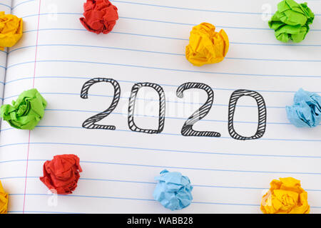 2020 New Year on notebook sheet with some colorful crumpled paper balls around it. Close up. - Stock Photo