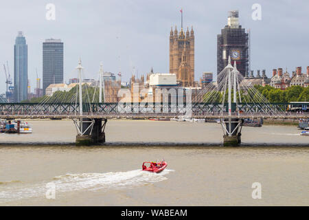 Thames rockets powerboat approaching the hungerford railway and golden jubilee foot bridges on the river thames, london, uk - Stock Photo