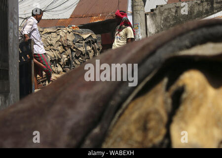 Dhaka, Bangladesh. 19th Aug, 2019. Workers carry rawhides after applying salt out of a warehouse at the Posta area in Dhaka.In the post-Eid few days, it has been a common scenario that traders at Posta area, which is known as wholesale market for rawhide, are busy processing rawhide by rubbing salt. Not only the rawhide traders but tanners are also busy buying rawhide from the wholesalers during Eid-ul-Azha. Credit: Sultan Mahmud Mukut/SOPA Images/ZUMA Wire/Alamy Live News - Stock Photo