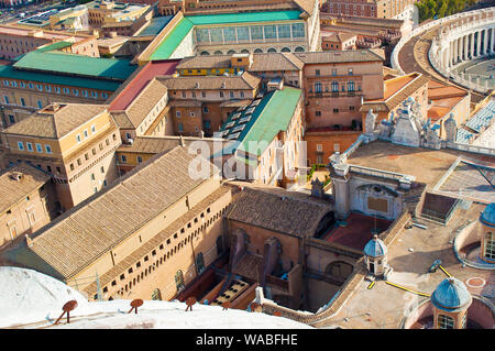 View of part of St. Peter's Square (Piazza San Pietro) and many columns among many orange rooftops and small towers in Vatican, Italy. Cozy courtyard. - Stock Photo