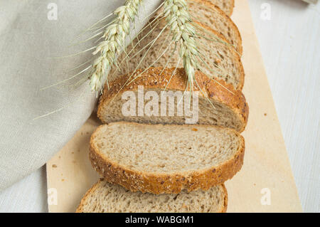 Fresh bread on a wooden chopping Board, wrapped in linen cloth, next to wheat ears, copy space, top view. Brown whole grain sliced bread, rustic backg - Stock Photo